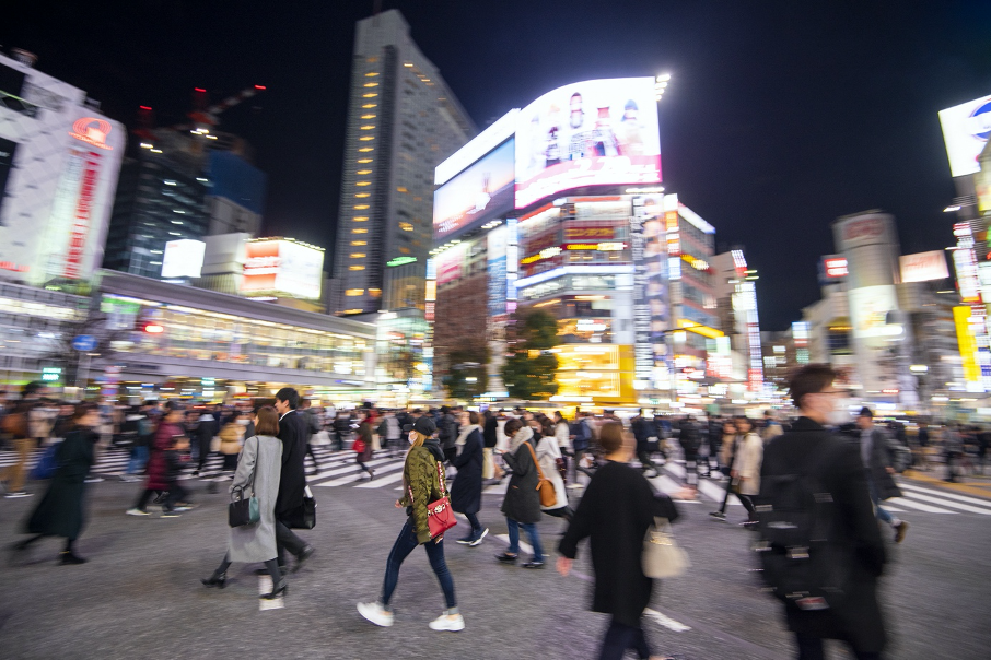 Image of busy city street at night with people walking past