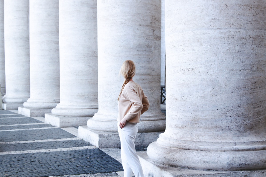 Blonde woman with braid facing away from camera next to a long row of columns