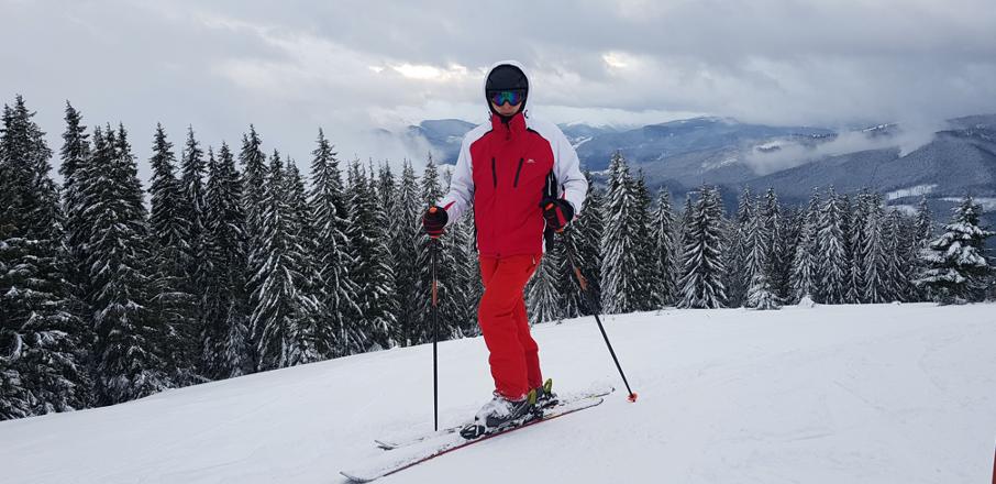 Igor in Bukovel on mountain top on skis wearing red ski suit