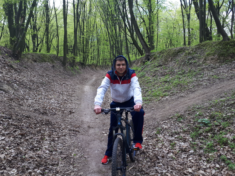 Igor in hooded jacket on bike on trail in Kyiv forest