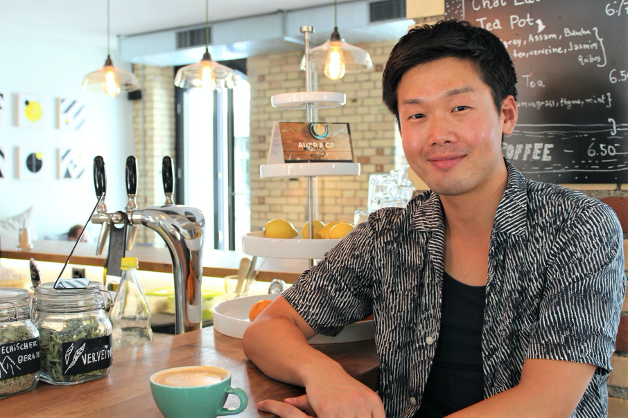 Head barista, Gaku sitting in his cafe with cappucino