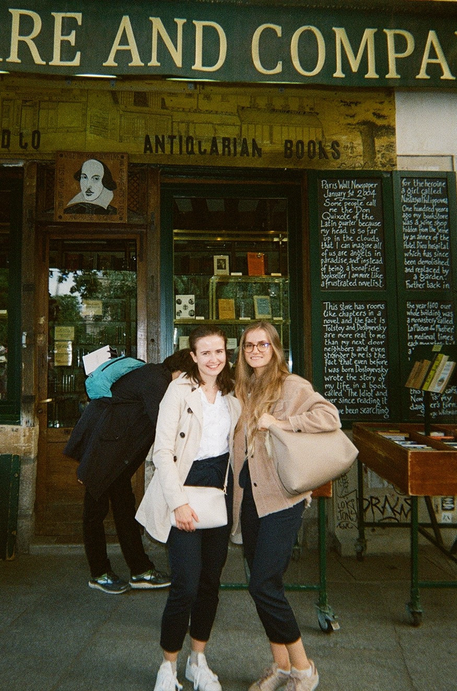 Two young women posing in front of Shakespeare and Company