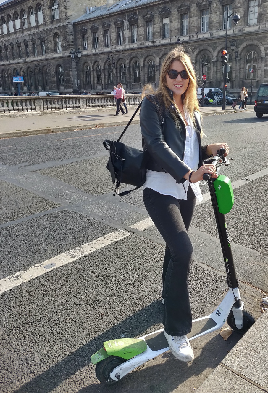 Woman in historic square posing with green and white electric scooter