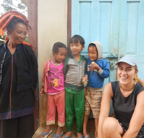 Casually dressed woman sitting on doorstep with woman and three children in Myanmar
