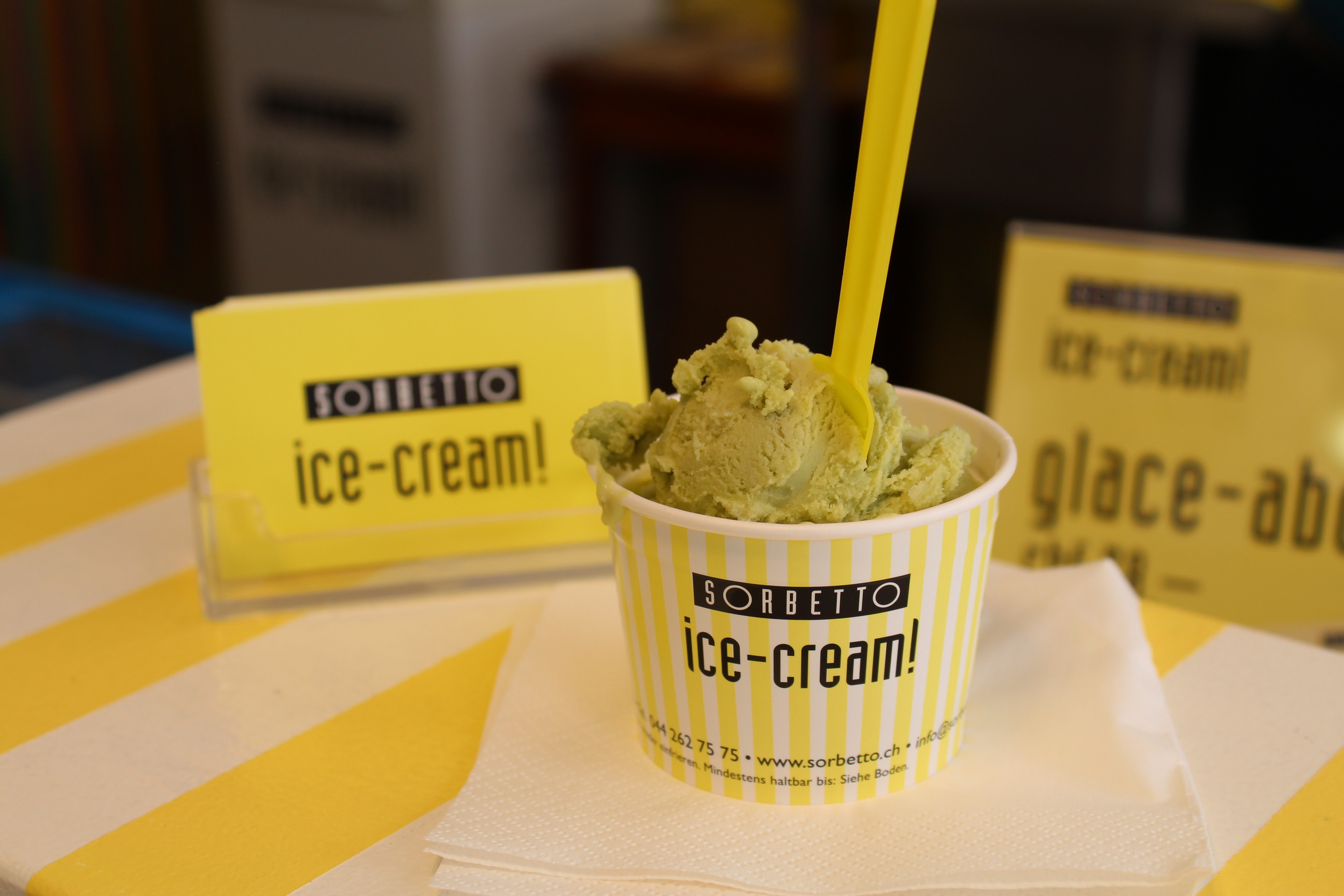 Green ice cream in bright yellow striped cup with long yellow spoon
