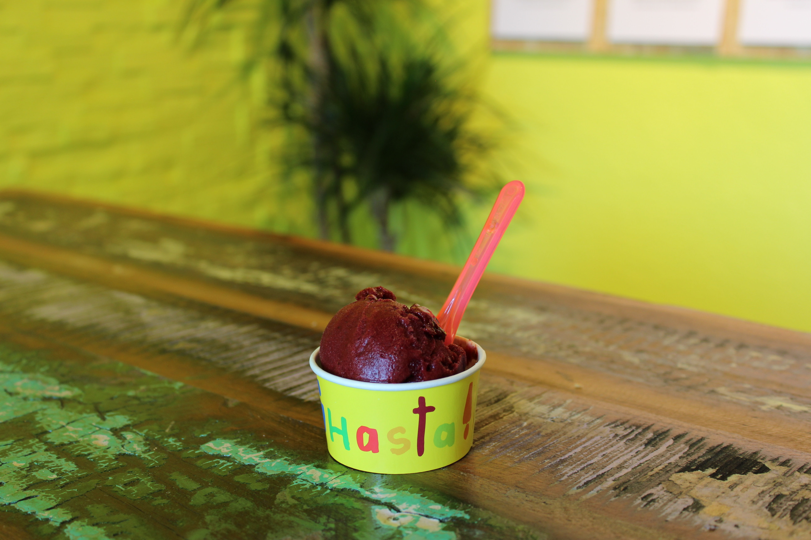 Small scoop of dark red ice cream in neon yellow paper cup