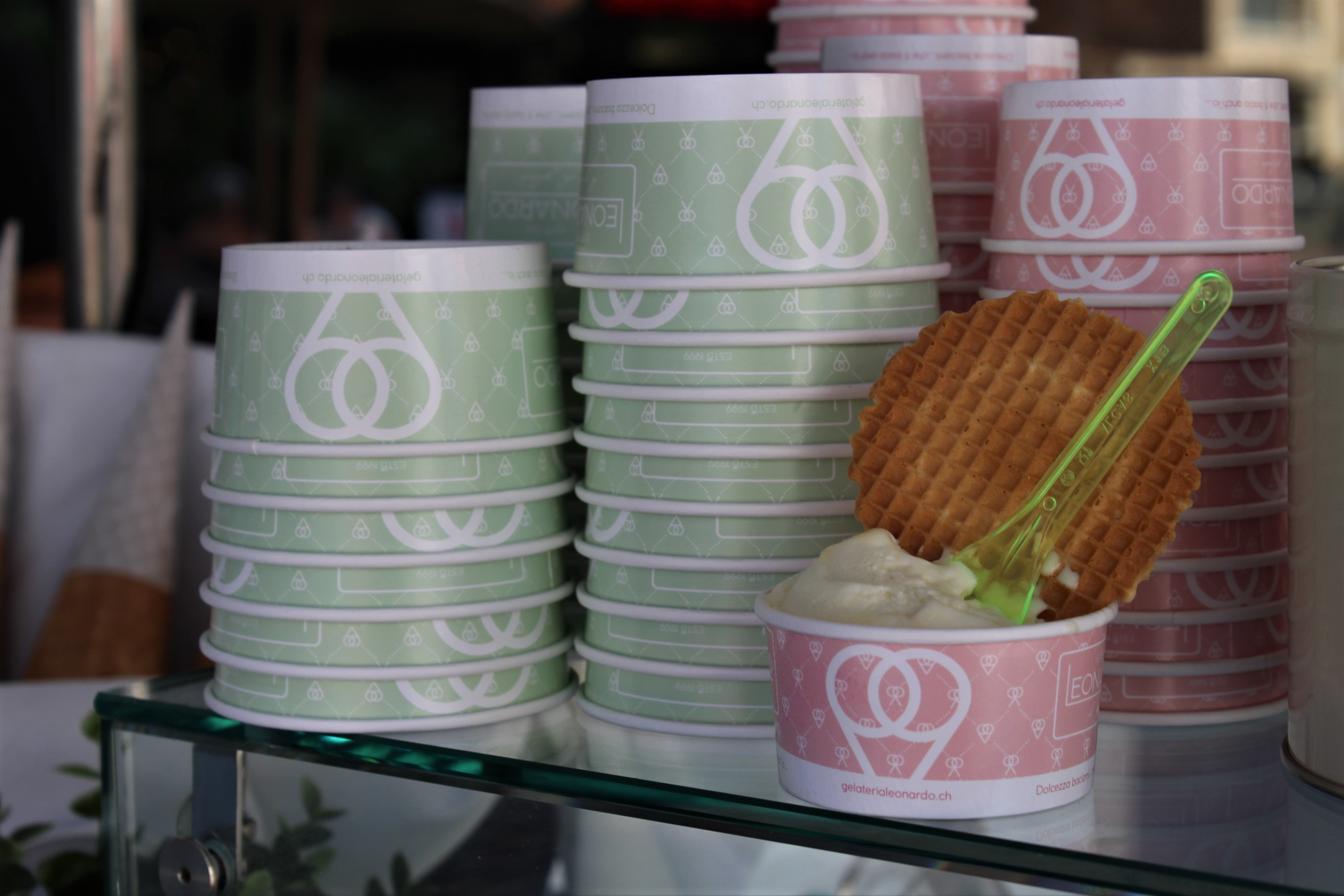 Small scoop of ice cream in front of stacks of pink and green paper cups
