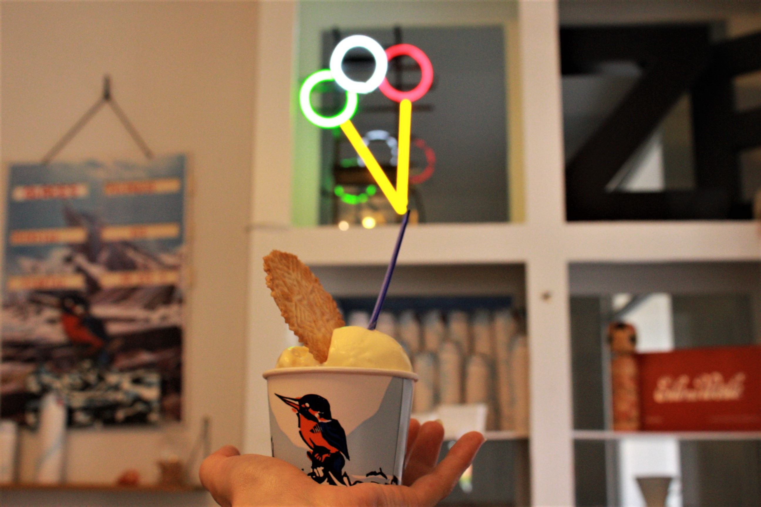 Hand holding small cup of ice cream with neon sign in back