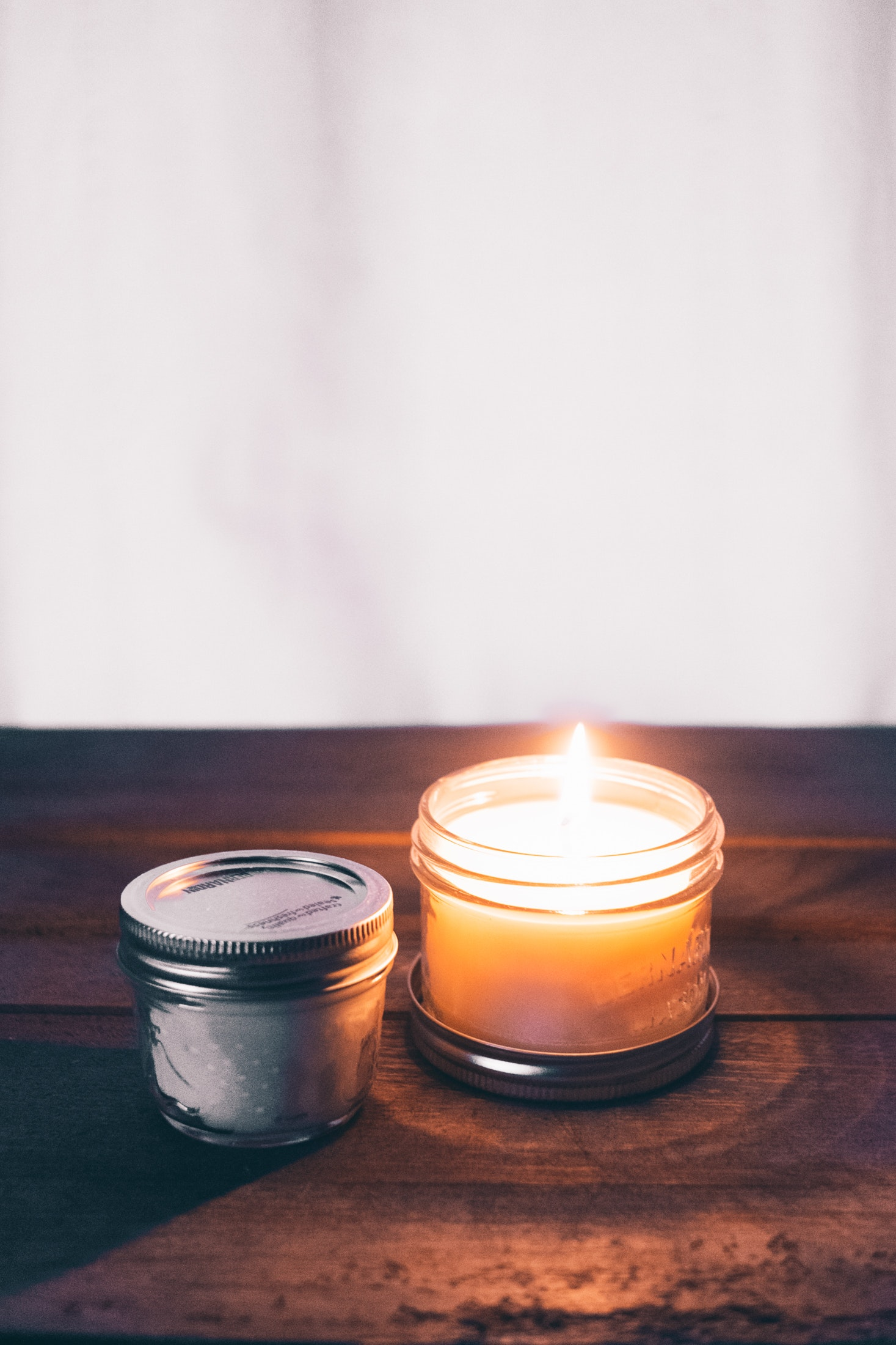 Simple image of candle in glass jar on table