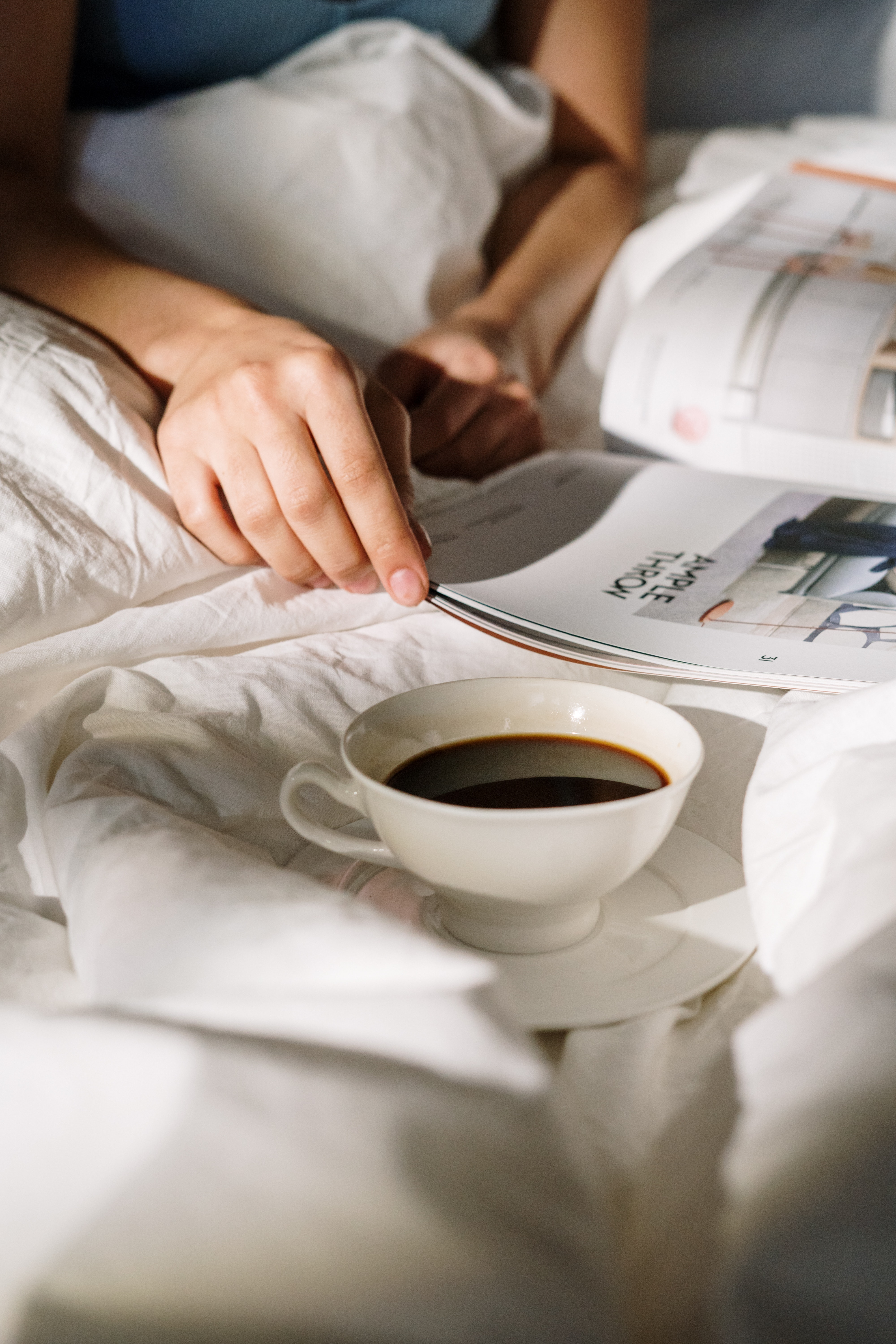 Close up of person in bed reading magazine with coffee cup