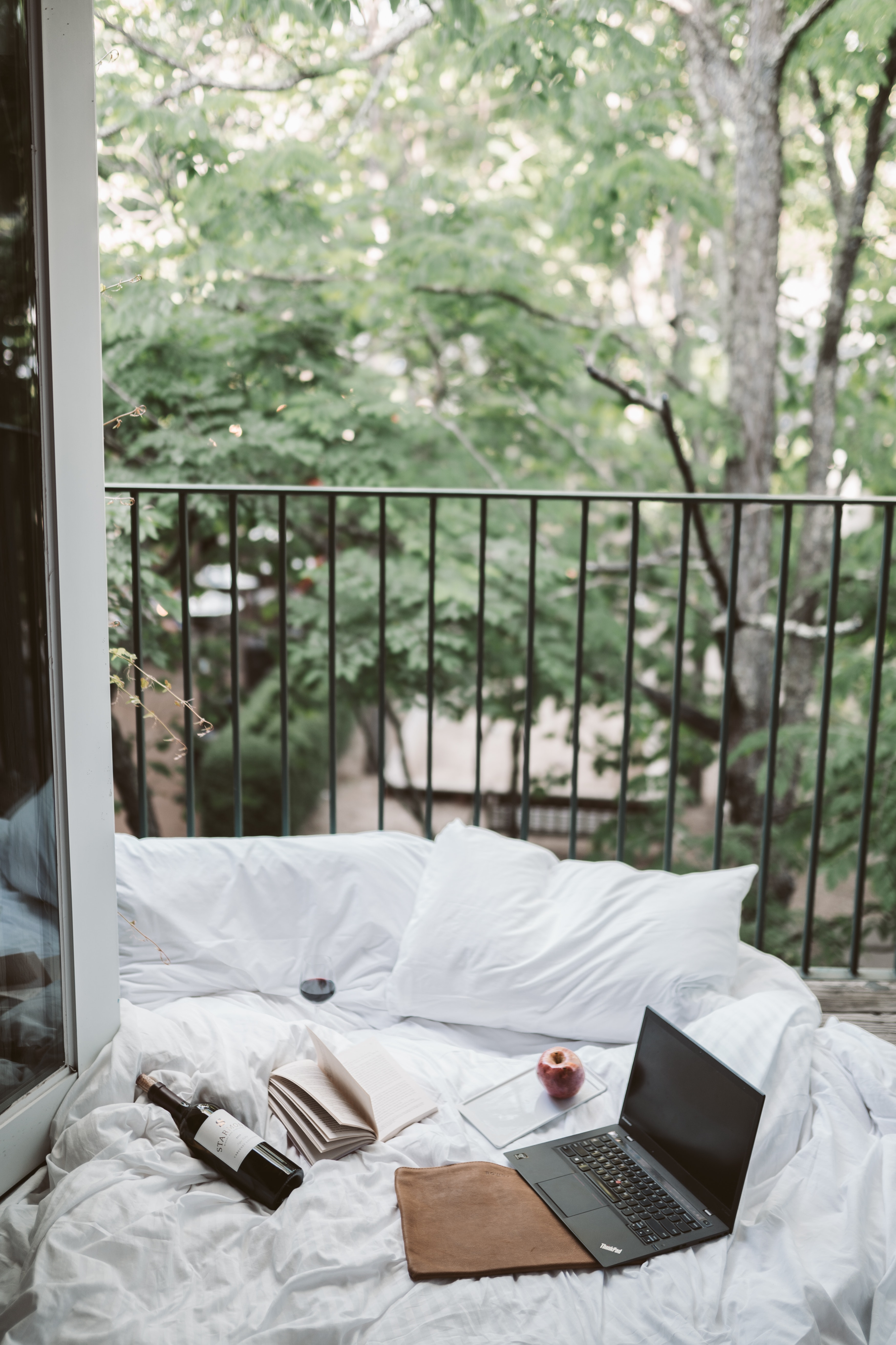 Laptop and wine bottle on cozy white settee on terrace